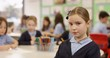 4K Portrait serious little girl in primary school classroom. Slow motion