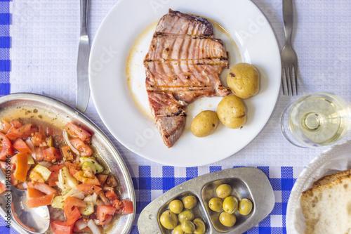 Foto op Aluminium Assortiment Tuna steak accompanied with potatoes, olives, tomato salad, bread and wine