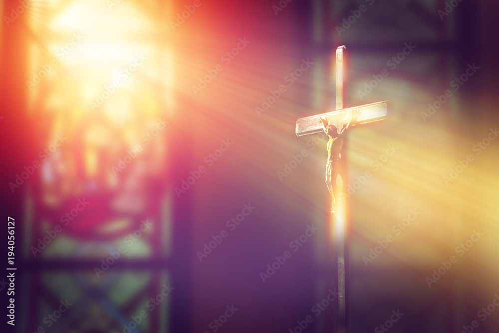 Fotografie, Obraz  crucifix, jesus on the cross in church with ray of light from stained glass