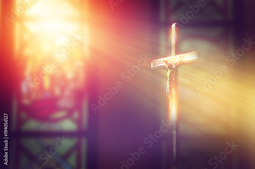 Vászonkép crucifix, jesus on the cross in church with ray of light from stained glass