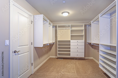 Cuadros en Lienzo  Large walk-in closet with white shelves, drawers
