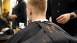 Barber cutting hair with scissors and hair flying in the air in slow motion. Back view of man in barber shop and flying hair in slow motion. Close-up back view of young bearded man getting beard
