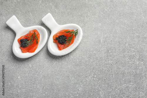 Tuinposter Voorgerecht Tasty appetizers with black caviar and salmon on grey background