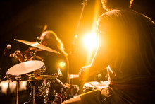 Drummer On Stage Playing With A Band With Gold Yellow Light Shining In Background