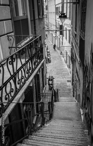 black-and-white-photo-of-old-narrow-crowdless-streets-of-the-old-genova-district-in-genoa-italy