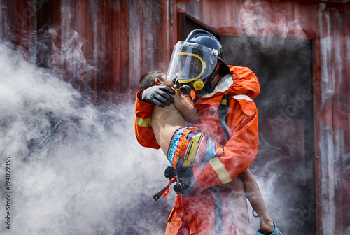 Fotografie, Obraz Emergency Fire Rescue training,Firefighters save the boy from burnt place