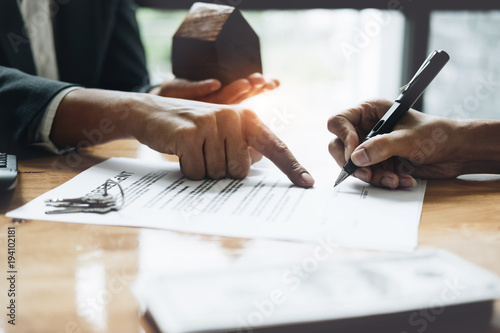 Fotografía  Businessman and estate agent signing a document for house deal, vintage filter e