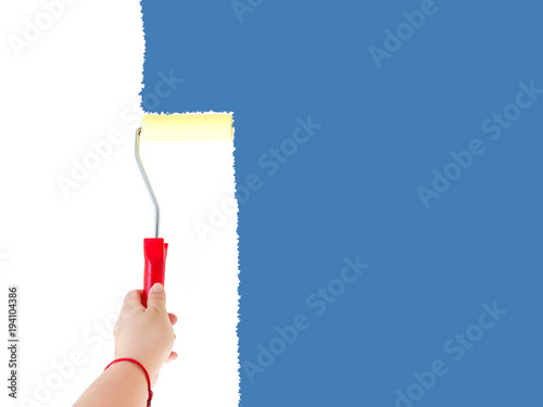 Fotografia  One person painting a white wall with a roller brush