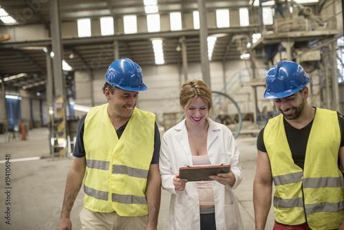 Mujer embarazada da instrucciones a los trabajadores de la factoría mediante una tablet