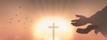 Resurrection Of Easter Sunday Concept: Silhouette Human Open Two Empty Hands With Palms Up And Birds Flying Over Blurred Cross In Church Background