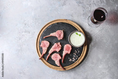 Grilled sliced rack of lamb with yogurt mint sauce served with glass of red wine, pink salt on round wooden slate board over grey texture background. Top view, space