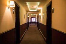 The Long Corridor In The Hotel With The Lamps Illuminated