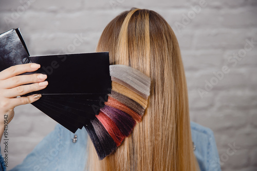 Obraz Master shows palette of hair colors on background of client's hair. - fototapety do salonu