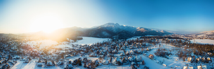 aerial view of a small snowy town and mountains in winter