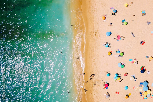 Poster Luchtfoto Aerial View From Flying Drone Of People Crowd Relaxing On Beach In Portugal