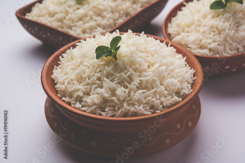 Cooked plain white basmati rice in terracotta bowl over plain or wooden backgrou Wallpaper Mural