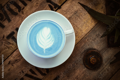 A white cup of hot milk butterfly pea latte art on the wooden table in coffee shop. Top view with retro filter effect