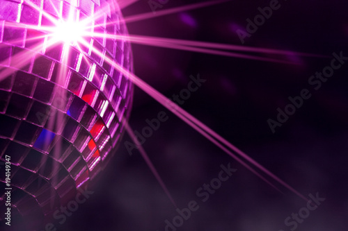 Disco ball with violet star burst and fog in club