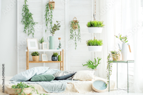 Fotobehang Planten Light room with a bed and a large window. Concept interior, decoration, comfort in the house.