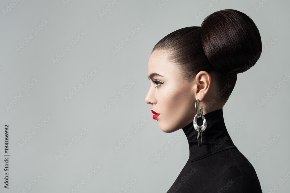 Fototapeta Fashion Portrait of Elegant Young Woman with Hair Bun Hairstyle and Eyeliner Make up. Cute Female Model wearing Black Roll Neck Jersey, Profile Portrait.