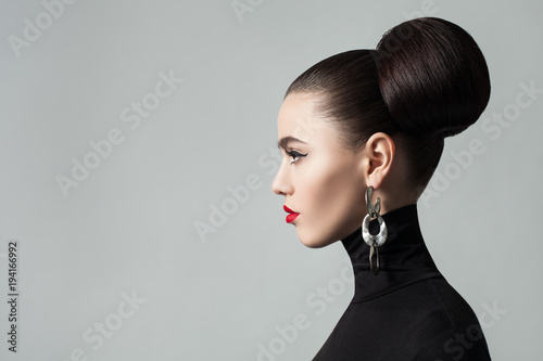 Tuinposter Kapsalon Fashion Portrait of Elegant Young Woman with Hair Bun Hairstyle and Eyeliner Make up. Cute Female Model wearing Black Roll Neck Jersey, Profile Portrait.