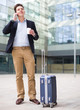 cheerful worker with baggage and talking phone