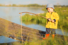 Young Little Boy Fishing From Wooden Dock