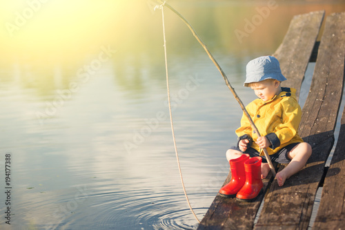 Fotografia, Obraz  Handsome Young Kid Holding his Fishing Rod