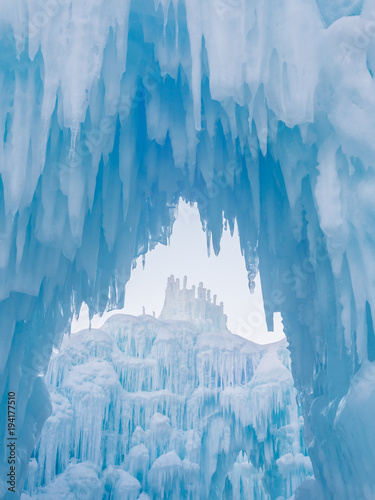 Tablou Canvas Winter ice castle caves with frozen icicles at sunset.