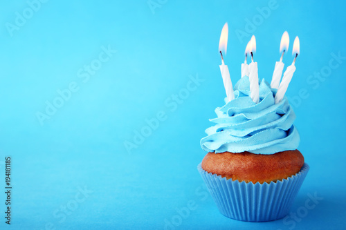 Photo  Tasty cupcake with candles on blue background