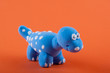 Camarasaurus. Blue dino model made of plasticine on orange background