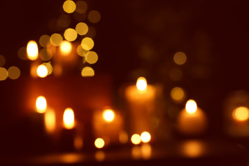 Blurred view of beautiful burning candles in darkness