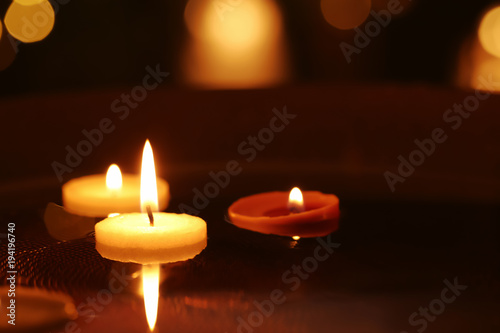 Recess Fitting Zen Small burning candles floating in plate with water, closeup