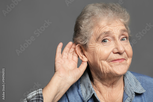 Fotografía  Elderly woman with hearing problem on grey background