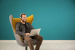 canvas print picture - Handsome man listening to music while sitting in comfortable armchair against color wall