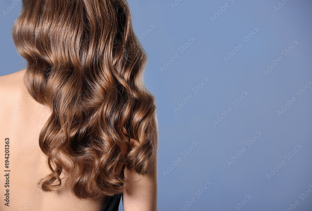Fototapeta Beautiful young woman with long wavy hair on color background