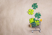 Shopping Trolley With Four-leaf Clover On Brown Paper Background. Copy Space.