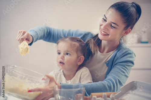 Poster Artist KB Mother and daughter in kitchen. Mother and daughter baking cookies together. Space for copy.