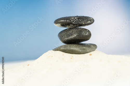 Foto op Canvas Stenen in het Zand Three black stones in the sand, blue sky background
