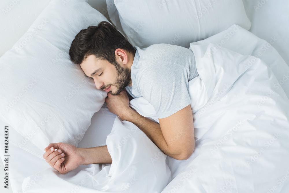 Fototapeta top view of bearded man sleeping on bed in bedroom