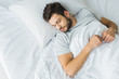 canvas print picture - top view of bearded man sleeping on bed