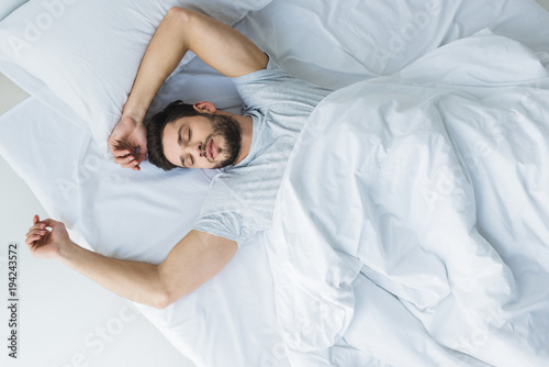 Obraz top view of handsome man sleeping on bed in bedroom - fototapety do salonu