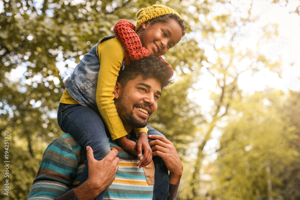 Fototapeta African American father with daughter on meadow.