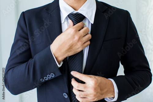 Carta da parati  People, business,fashion and clothing concept - close up of man in shirt dressing up and adjusting tie on neck at home