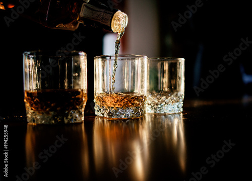 Photo Man pours whisky in the glasses standing before a wooden table