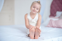 Little Blonde Girl Sitting On The Bed With Focus On The Feet Indoors