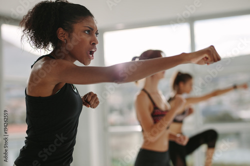 Strong young females exercising in gym