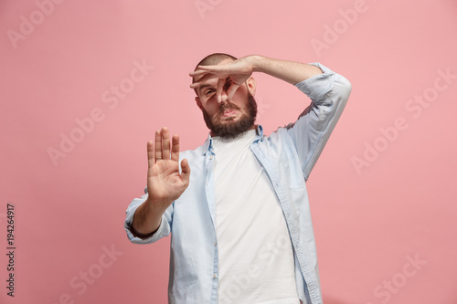Young man with disgusted expression repulsing something, isolated on the pink Fototapeta