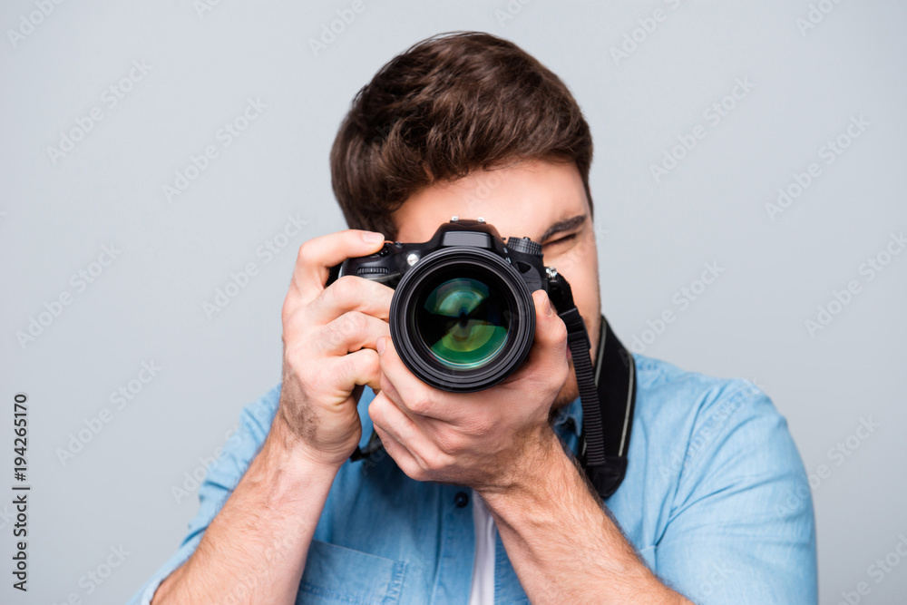 Fototapety, obrazy: Portrait of guy in jeans shirt looking at photo camera, shooting photographs during excursion, making photosession over gray background