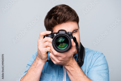 Obraz Portrait of guy in jeans shirt looking at photo camera, shooting photographs during excursion, making photosession over gray background - fototapety do salonu
